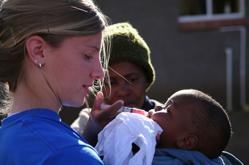Peace Corp volunteer feeding an infant